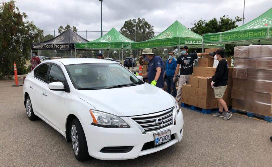 Volunteers with the San Diego Food Bank help load food into cars at the Mira Mesa Senior Center on June 17, 2020