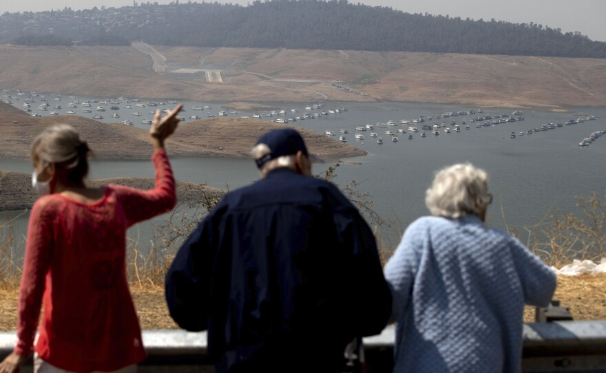 In this Aug. 22, 2021, file photo, visitors look out over Lake Oroville as water levels remain low due to continuing drought conditions in Butte County, Calif.