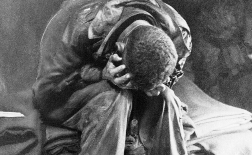 An American soldier collapses in his hands from the strain of fighting along the Taegu front, South Korea, 1950.