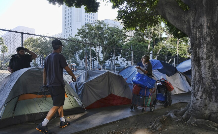 In this Monday, July 1, 2019 file photo, homeless people move their belongings from a street along side of Los Angeles City Hall as crews prepared to clean the area.