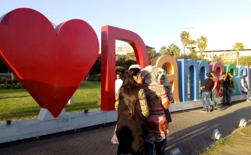 """Young people pose at """"I Heart Damascus"""" in Omayyad Square, in the capital of Syria."""