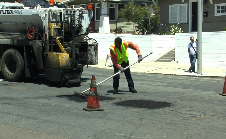 A San Diego worker fills a pothole in the South Park neighborhood on April 29, 2014.