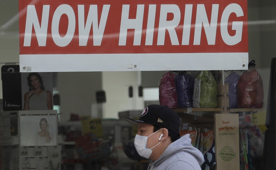 A walks by a CVS Pharmacy in San Francisco on May 7. U.S. employers unexpectedly added jobs last month as the unemployment rate fell.