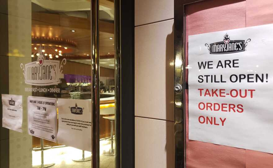 A sign in front of MaryJane's restaurant in downtown San Diego on May 5, 2020, shows the eatery is still open for takeout orders while still closed for sit-in dining because of the coronavirus pandemic.