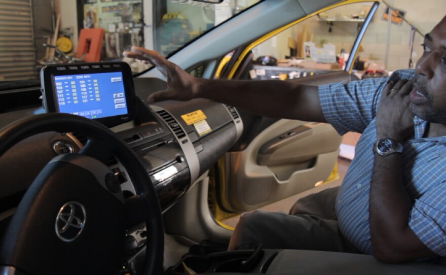 A Yellow Radio Service employee points to a new GPS system being installed in all Yellow Cabs Aug. 7, 2014. MTS requires cab companies to outfit their vehicles with a long list of equipment and signage, even stipulating their dimensions and placement in the car.