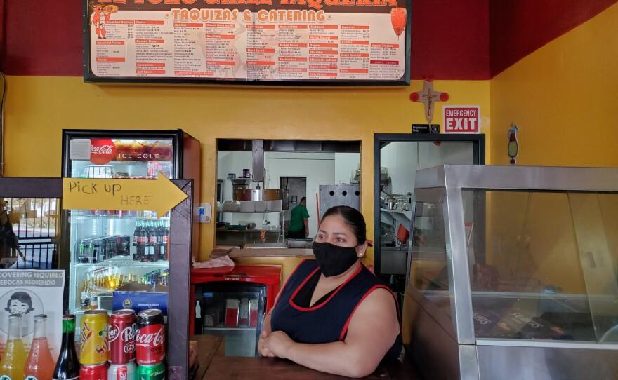 Maribel Estrada stands at the counter of her City Heights restaurant El ToroGrill Taqueria, Feb. 25, 2021.