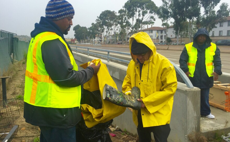 Brandon Smith (left) with the Alpha Project outreach team gives a homeless man a pair of rain boots and a rain jacket ahead of forecasted heavy rains in San Diego, Jan. 4, 2016.