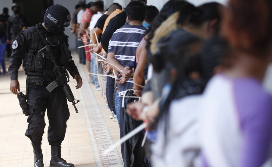 A policeman of the anti-gang unit inspects handcuffed alleged members of the Mara Salvatrucha detained during a police raid in San Salvador, El Salvador, Friday, Jan. 31, 2014.