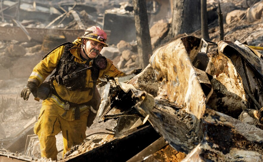 Firefighter Jesse Viescas searches through a residence at Cache Creek Mobile Home Estates where the Cache Fire leveled dozens of homes, Wednesday, Aug. 18, 2021, in Clearlake, Calif.
