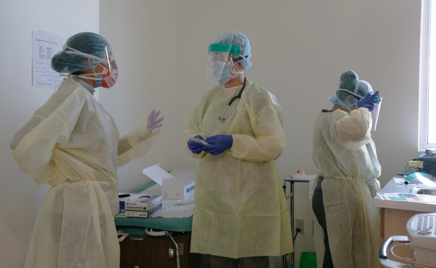 Healthcare workers are shown in a room where they change into clean personal protective equipment at La Maestra Community Health Centers' City Heights clinic, April 8, 2020. Due to PPE shortages, workers wipe down face shields to reuse them rather than replacing them after each use.