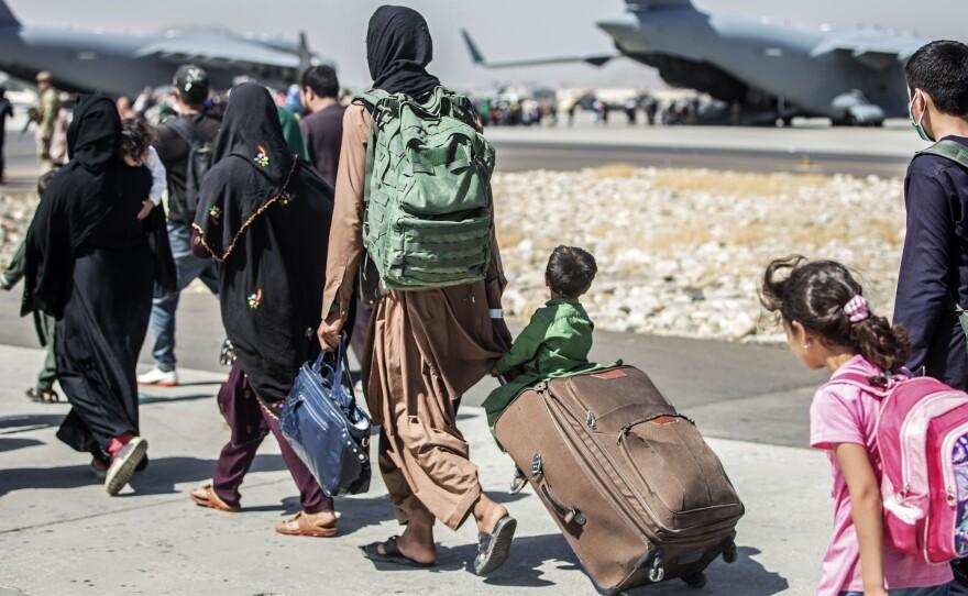 Families walk toward their flight during evacuations at Hamid Karzai International Airport in Kabul, Afghanistan, on Tuesday.