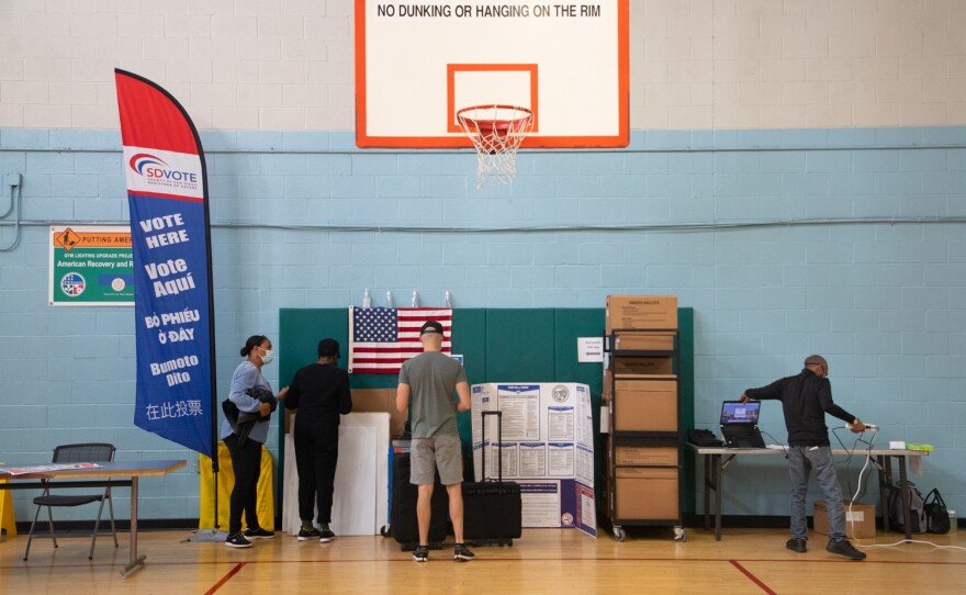 Poll workers set up for the start of in-person voting at the Mid-City Gym in City Heights, Oct. 30, 2020.