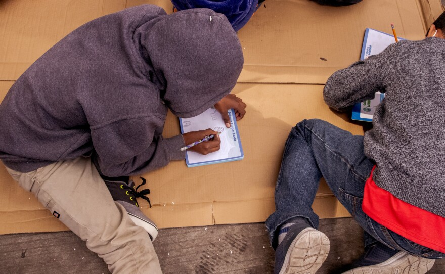 Students do school work on the ground at a school started by asylum seekers for the children of asylum seekers holds class at the migrant camp in the El Capparal plaza on Mexican side of the San Ysidro Port of Entry, March 12, 2021.