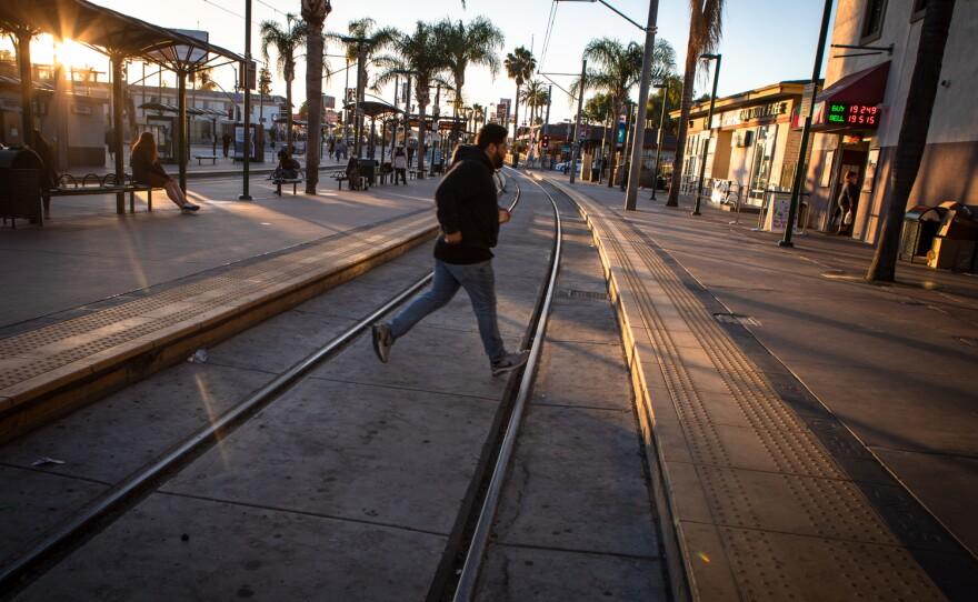 A man runs across the trolley tracks at the San Ysidro Transit Center, June 25, 2021.