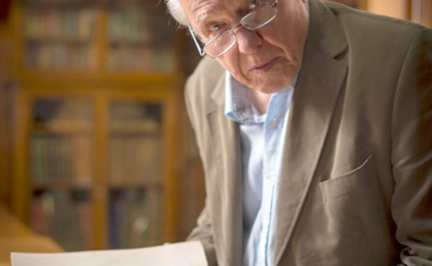 Sir David Attenborough with a book opened to a print of a flightless bird called a cassowary.
