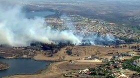 A brush fire burns off Otay Lakes Road, near Woods Drive, in Chula Vista, June 26, 2015.
