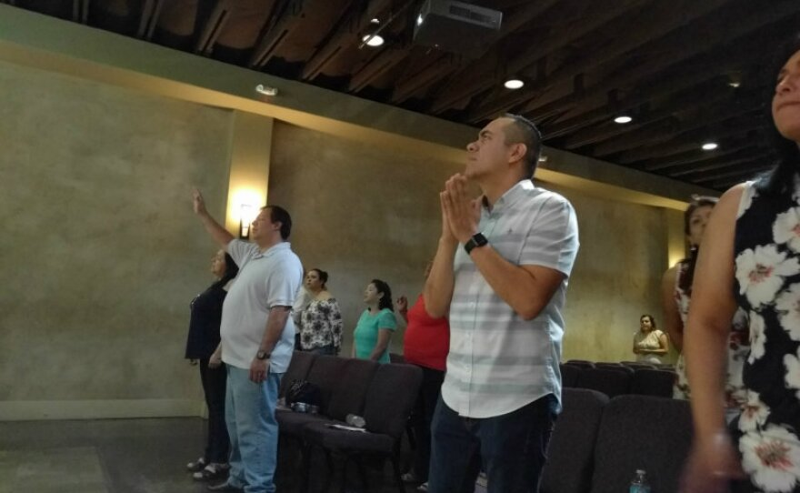 Alex Vaiz, senior pastor of Vida Church holds his hands in prayer, during a Sunday service in this undated photo.