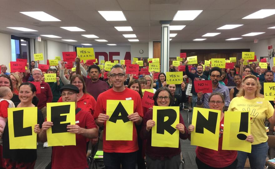 San Diego Education Association members hold up signs in support of a new union contract, March 9, 2017.