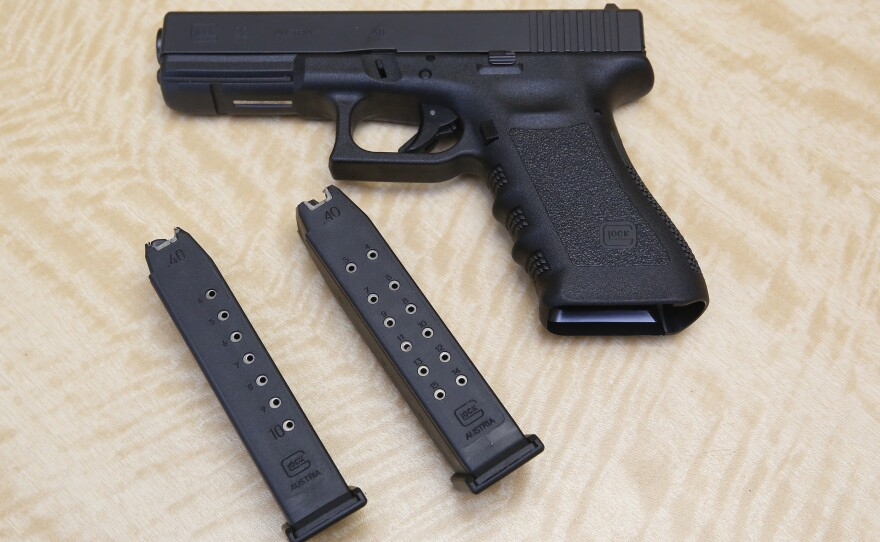 A semi-automatic hand gun is displayed with a 10 shot magazine, left, and a 15 shot magazine, right, at a gun store in Elk Grove, Calif., Tuesday, June 27, 2017 photo.