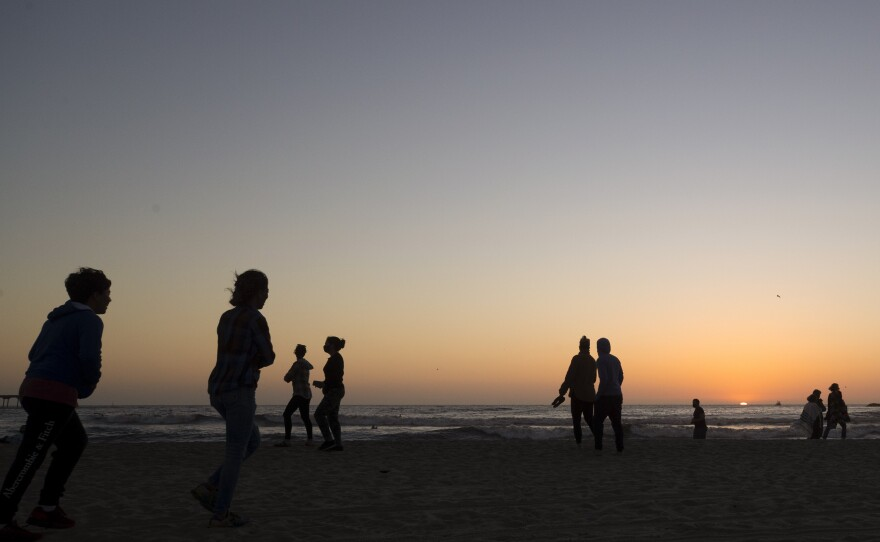 People keep apart along Ocean Beach at sunset Monday, May 4, 2020, in San Diego, during the coronavirus pandemic.
