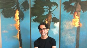 Artist Perry Vasquez sits in his studio in front of three of his burning palm tree oil paintings.