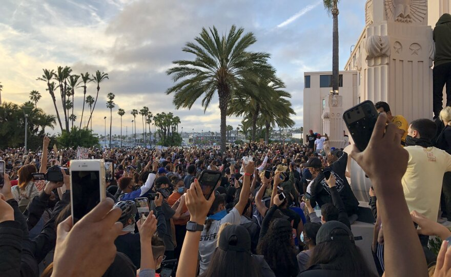 Protesters hold up their fists during a demonstration at San Diego's Waterfront Park, May 31, 2020.