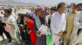 A man holds a certificate acknowledging his work for Americans as hundreds of people gather outside the international airport in Kabul, Afghanistan, Tuesday, Aug. 17, 2021.