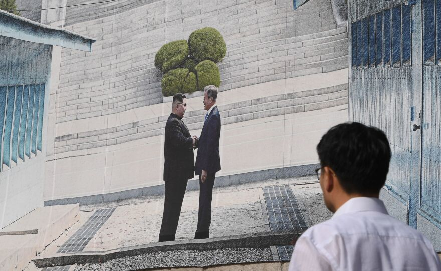 A man walks past a giant banner showing a picture of the summit handshake between South Korean President Moon Jae-in and North Korean leader Kim Jong Un, at Seoul City Hall on Sept, 13. Moon will fly to North Korea's capital on Sept. 18 for a third summit with Kim.