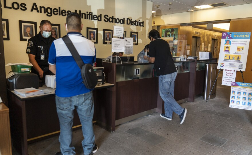 Visitors wait in line to be screened by security before being allowed to enter the Los Angeles Unified School District administrative offices in Los Angeles Thursday Sept. 9, 2021.