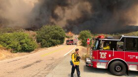 Firefighters block the road as the flames from the Valley Fire burn behind them. The wildfire is located at Japatul Road and Carveacre Road, southeast of Alpine in San Diego County. Sept. 6, 2020.