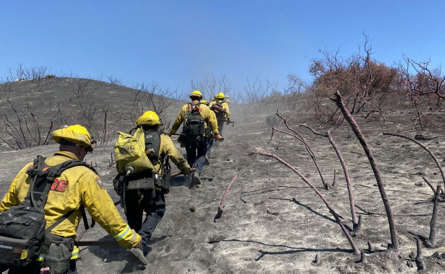 Firefighters patrol the fireline and mop up hot spots at the Chapparral Fire, which strandles San Diego and Riverside counties. Aug. 31, 2021.