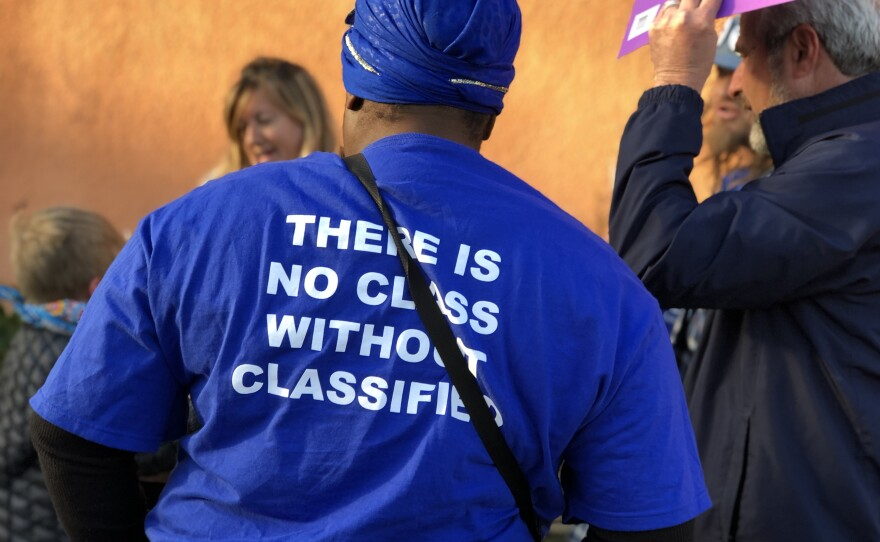 """A woman wears a shirt that reads, """"There is no class without classified,"""" outside of a San Diego Unified School Board meeting where trustees heard a proposal to cut classified jobs, Feb. 27, 2018."""
