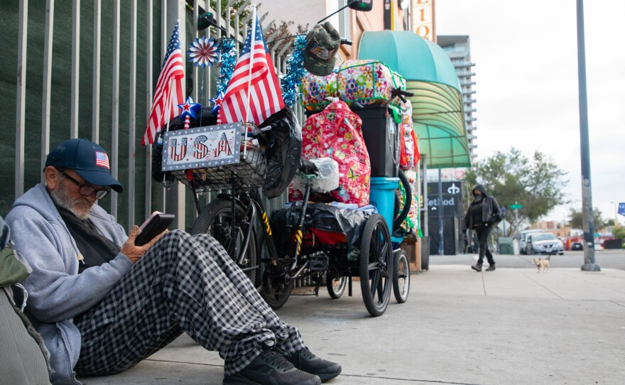 Eddie Richardson, who says he's a Vietnam War veteran, looks at his phone while sitting next to his bike on 16th Street in San Diego, May 20, 2020.