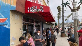 Customers line up outside of Hodad's in Ocean Beach during the Memorial Day weekend holiday on May 25th, 2020.