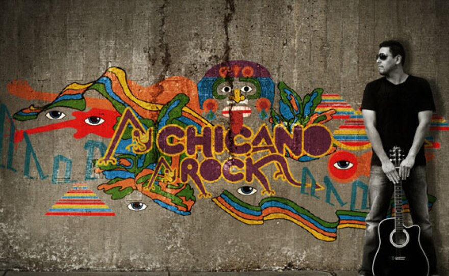 """A man with a guitar standing next to a colorful street mural that reads """"Chicano Rock."""" Design by eatdrink and James Adamé."""