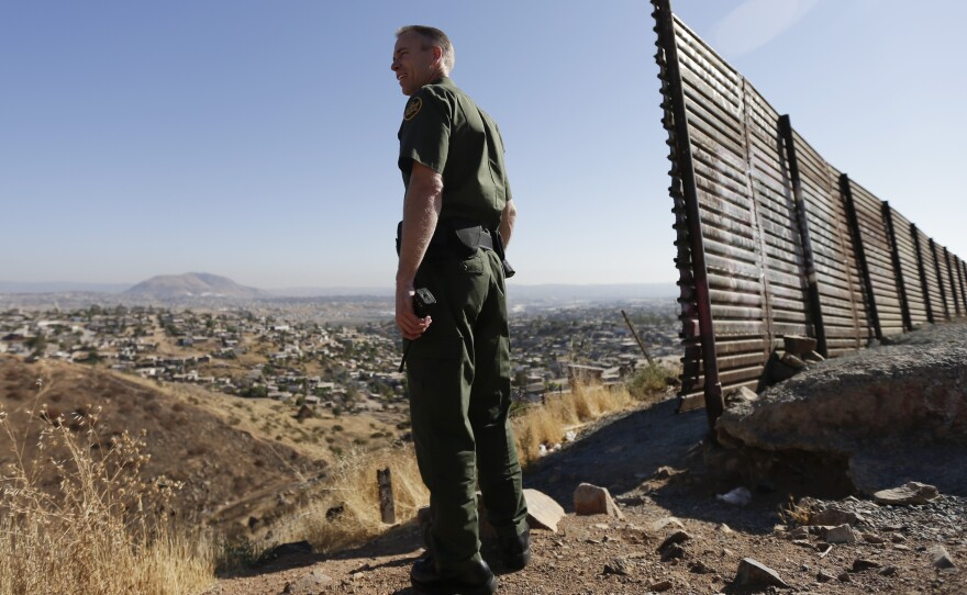 A U.S. Border Patrol agent looks out over Tijuana, Mexico, next to a portion of the U.S.-Mexico border wall.