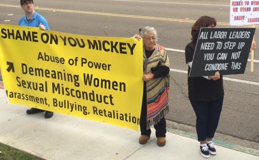 Protesters hold signs in opposition to Mickey Kasparian, May 9, 2017.