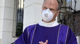 Deacon Dave Warren wears an N95 surgical mask with the mark of the ashen cross smudged in the middle of his forehead, Feb. 17, 2021.
