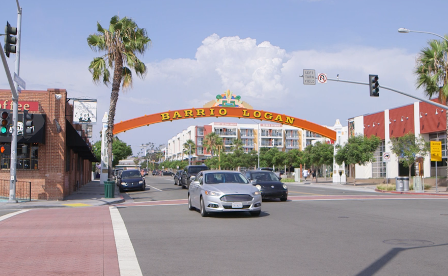 Cars pass under the Barrio Logan sign on July 30, 2015.