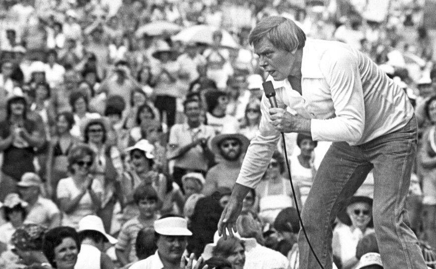 Singer Tom T. Hall leans to the edge of the stage at the Jamboree in the Hills near St. Clairsville, Ohio, in July 1977.