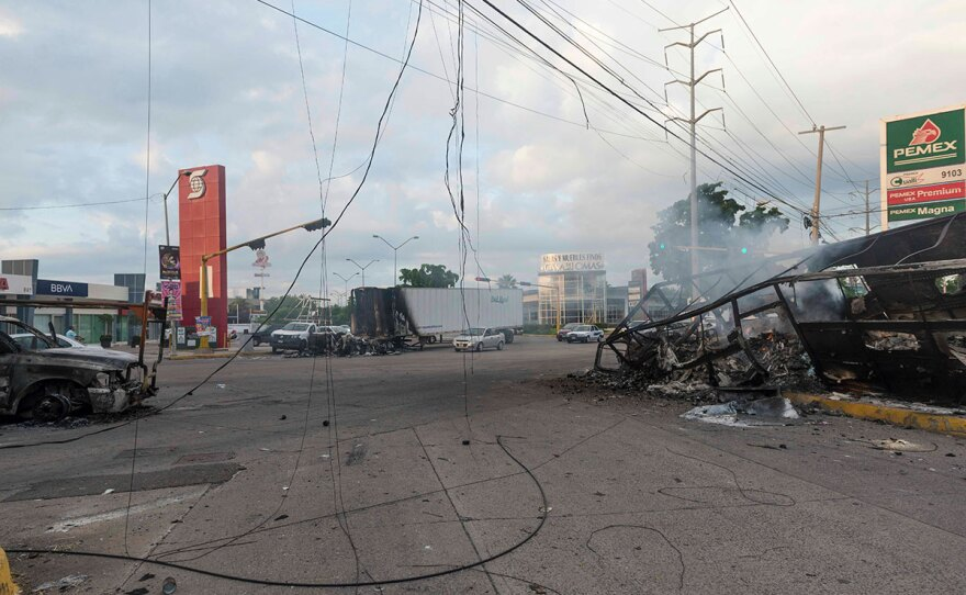 Burnt out vehicles used by gunmen smolder on an intersection, a day after street battles between gunmen and security forces in Culiacan, Mexico, Friday Oct. 18, 2019.