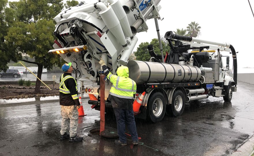 City workers pump sewers during a rainstorm in order to prevent flooding in San Diego, Dec. 4, 2019.