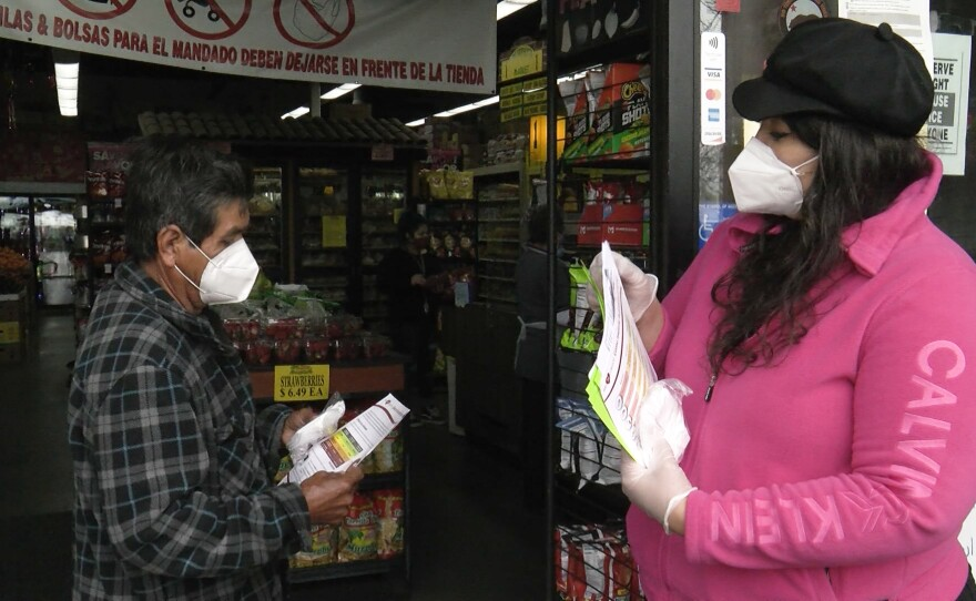 A community health worker, or promotora in Spanish, talks with a man outside Murphy's Market in City Heights, Feb. 12, 2021.