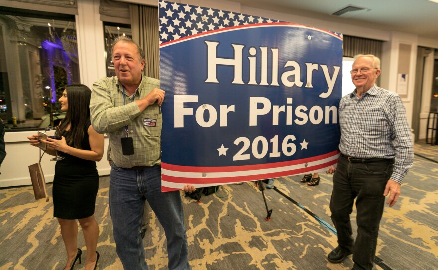 """San Diegans carry a """"Hillary For Prison 2016"""" sign at the U.S. Grant Hotel, Nov. 8, 2016."""