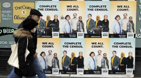 In this April 1, 2020, file photo, people walk past posters encouraging participation in the 2020 Census in Seattle's Capitol Hill neighborhood.