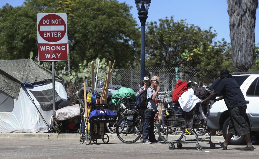 Homeless people crowd a parkway with tents and makeshift housing in San Diego, July 6, 2016.