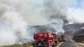 Fire trucks working to extinguish flames from the Pasqual Fire in San Pasqual Valley, July 26, 2018.