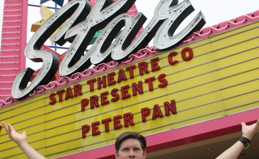 David Schulz, managing artistic director for Star Theatre Company, is pictured in front of the theater's neon sign, July 2, 2015.