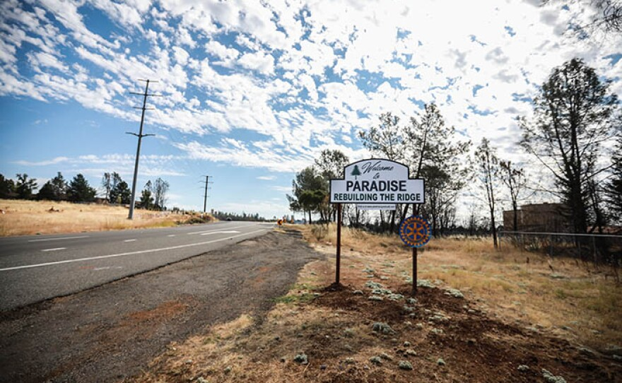 """A sign on the side of the road reads """"Welcome to Paradise - Rebuilding The Ridge."""""""