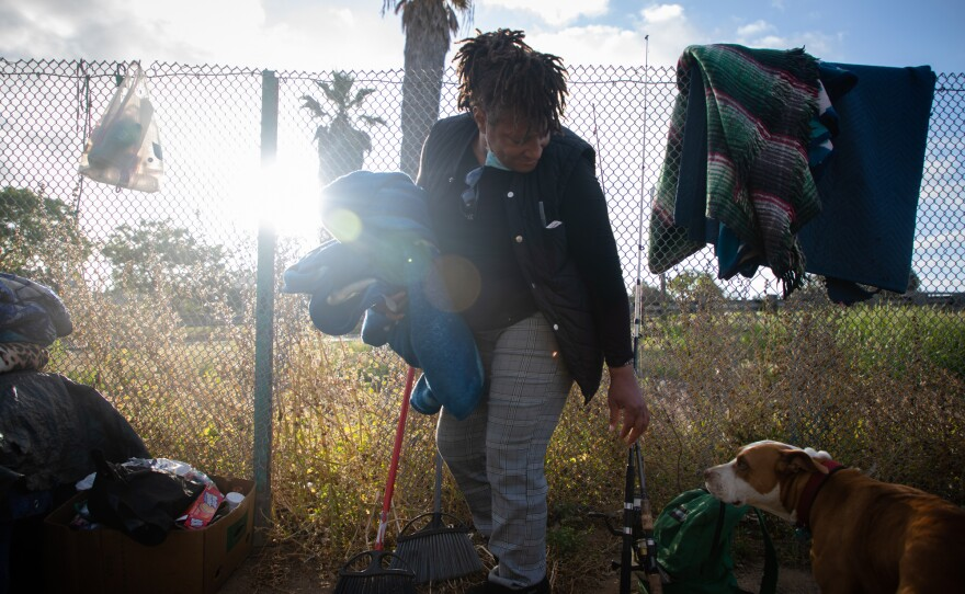 Wanita Long packs up blankets after sleeping on an area of dirt near the Interstate 5 ramp at 17th Street in San Diego, May 20, 2020.